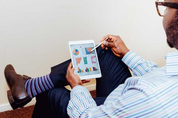Man looking at graphs on a tablet device