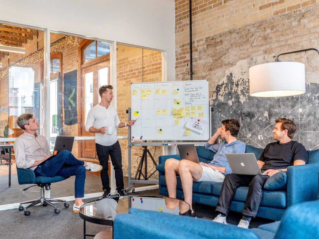 Image shows people talking and looking at a big white board