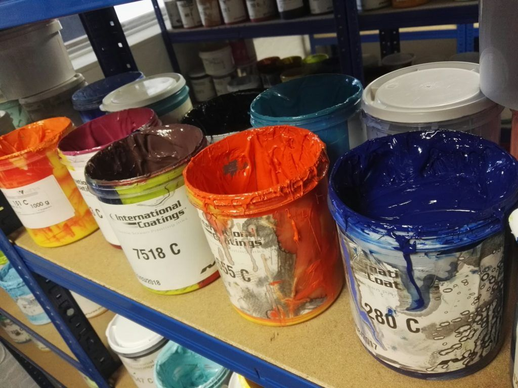 Image shows pots of paint used for screen printing